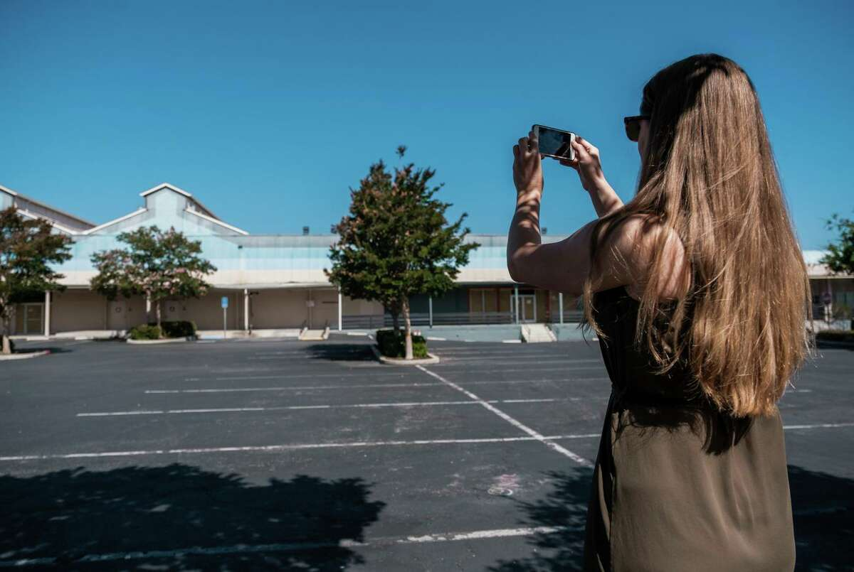 Kelsey Banes, executive director of Peninsula For Everyone, photographs a closed electronics store and surrounding parking lot that could be used for multifamily housing in Palo Alto.