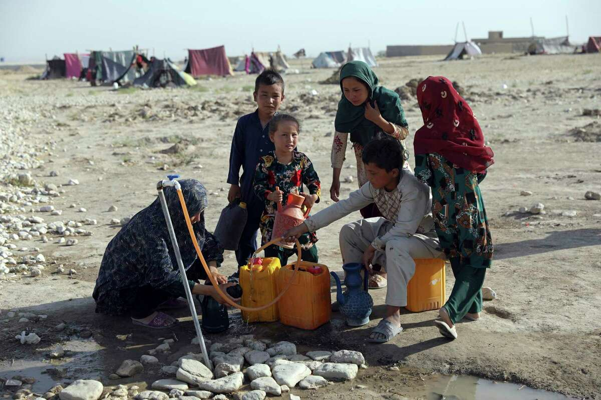 Internally displaced Afghans, who fled their home due to fighting between the Taliban and Afghan security personnel, fill water containers at a camp. There are many humanitarian reasons for a continued U.S. presence.
