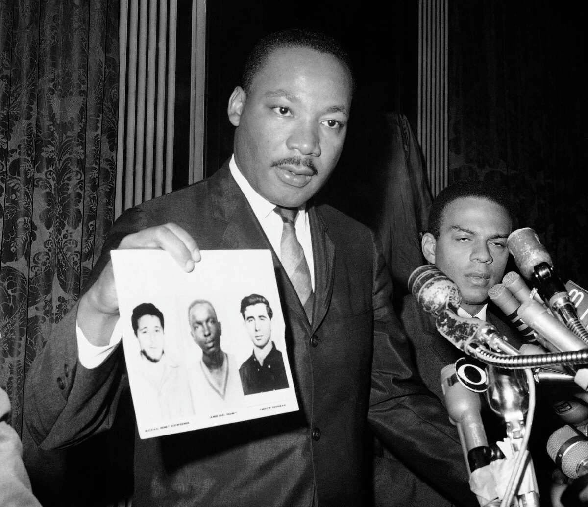 Martin Luther King Jr. holds up the photos of murdered civil rights workers Michael Schwerner, James Chaney, and Andrew Goodman. They died fighting to expand the right to vote. Nearly 60 years later, voting rights are under assault.