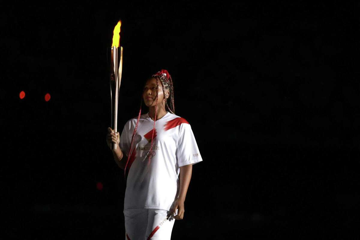 Naomi Osaka of Team Japan carries the Olympic torch towards the Olympic cauldron during the Opening Ceremony of the Tokyo 2020 Olympic Games at Olympic Stadium on July 23, 2021 in Tokyo.