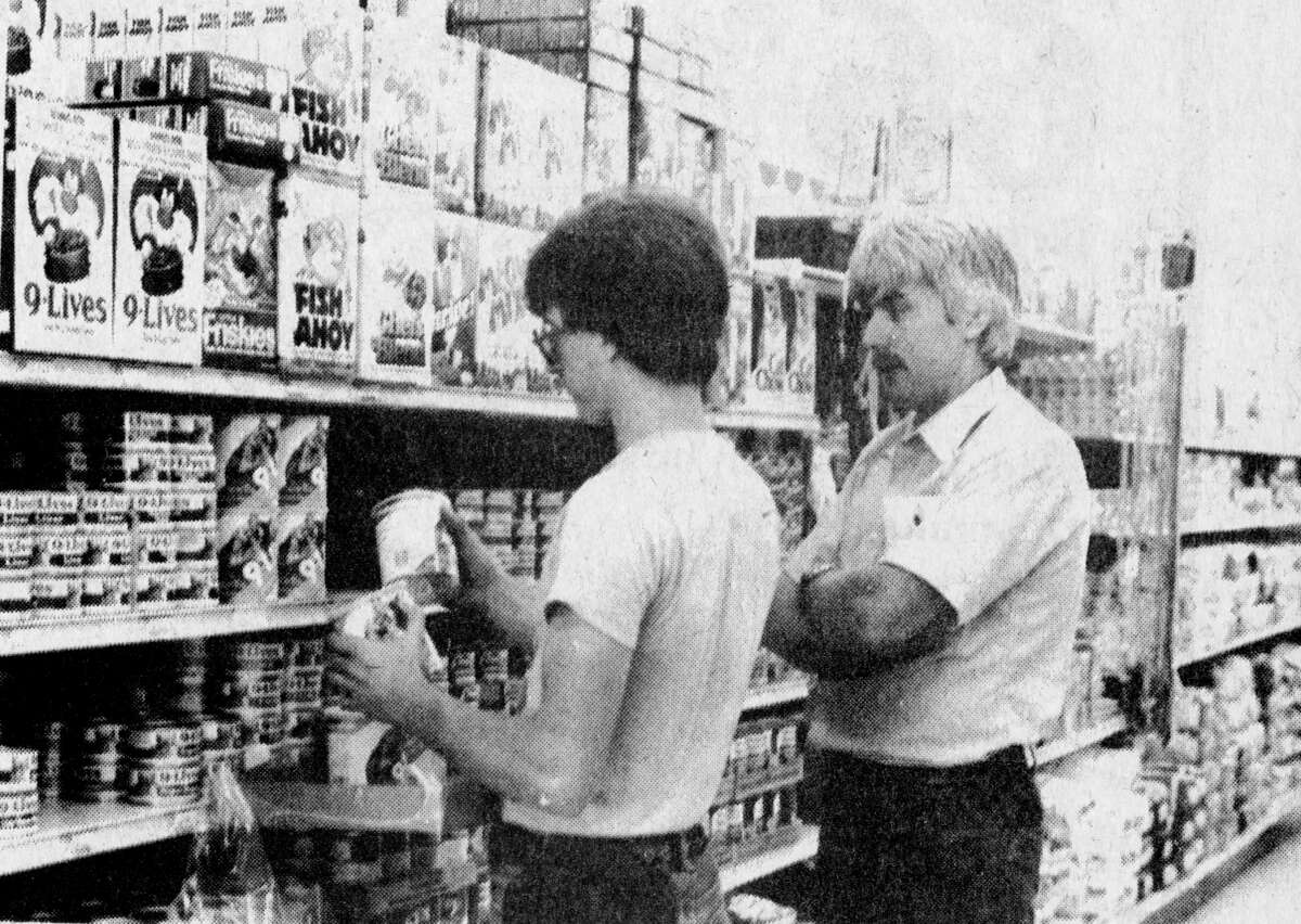 Oleson Food Store manager Tim Slack (right) checks on some stock being placed on the shelves by clerk Scott Modjeski. The Traverse City-based grocery chain will be employing 35 persons in its new Manistee store. Cashiers are preparing for the grand opening on July 28, 1981. The photo was published in the July 27, 1981 issue of the News Advocate. (Manistee County Historical Museum photo)