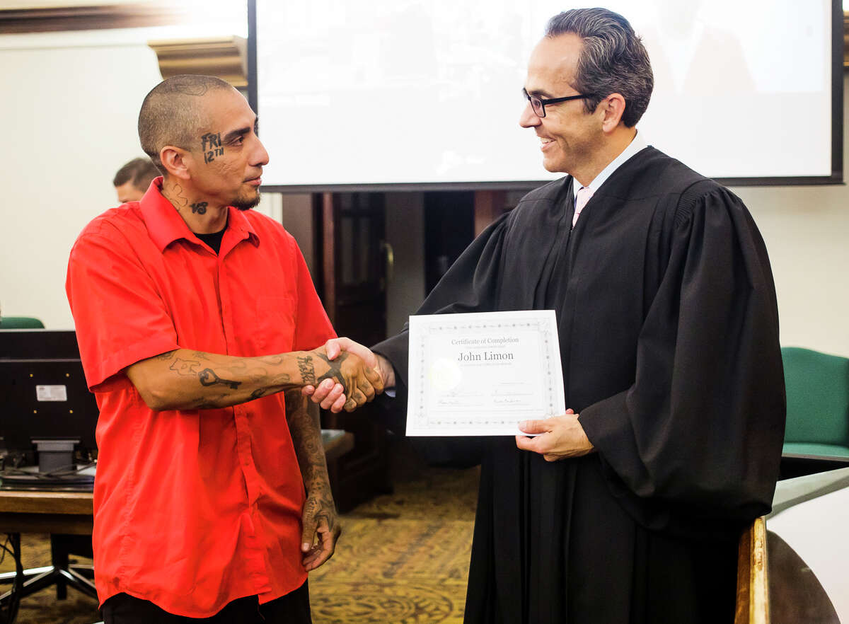 John Limon receives a certificate from Judge Stephen Carras during his graduation ceremony from the Midland County Honest Opportunity Probation with Enforcement (MiHOPE) program Friday, July 23, 2021 at the Midland County Courthouse. (Katy Kildee/kkildee@mdn.net)