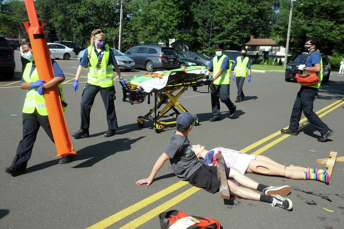 Members of Trumbull Emergency Medical Services worked with a group of students during a mass casualty training drill in Trumbull on Friday. The students worked as first responders in a scenario where they helped numerous people injured by an out-of-control motor vehicle.