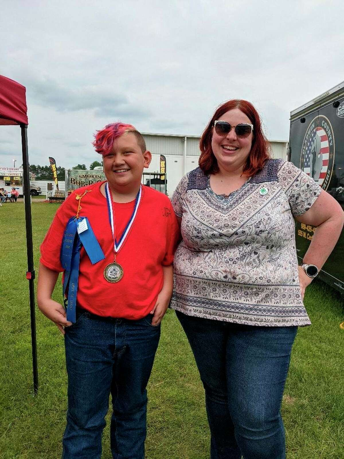 Logan Trevillian, 12, left with Missy Preston, Gladwin County 4H coordinator at the Gladwin County Fair last week. Trevillian earned $500 for his cookies at a 4H baking contest. The money joins his savings for a farm-to-table restaurant. He is saving to buy 100 acres to house livestock and crops. (Photo by Tereasa Nims/for the Daily News)