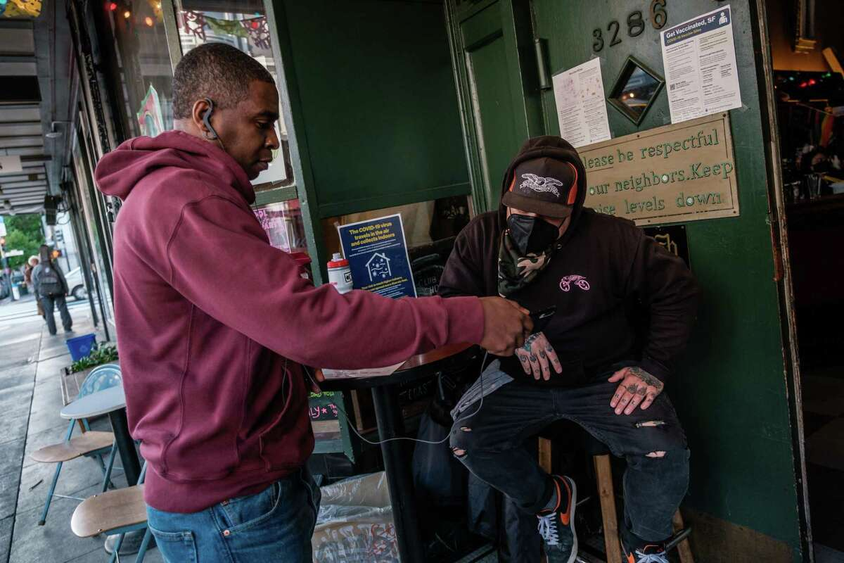 Manny B. shows proof of vaccination to doorman Jason Voisine at the Latin American Club in S.F.. Despite some misinformation spreading online, it's legal for restaurants and bars to become vaccinated-only establishments.