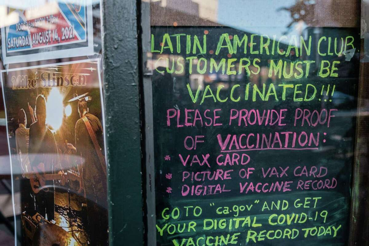 A sign asking all patrons to show proof of vaccination is seen in a window outside of the Latin America Club in San Francisco on Thursday, July 22, 2021. The Latin American Club is one of many bars and restaurants in the city that are now requiring proof of vaccination before entering.