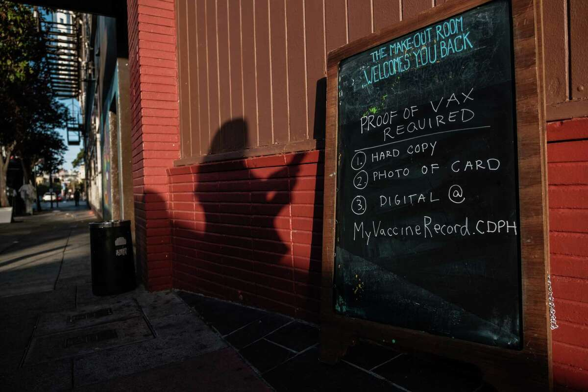 The silhouette of a woman preparing to show a photo of her vaccination card is seen next to a sign asking all patrons show proof of vaccination at the Make Out Room in San Francisco on Thursday, July 22, 2021.