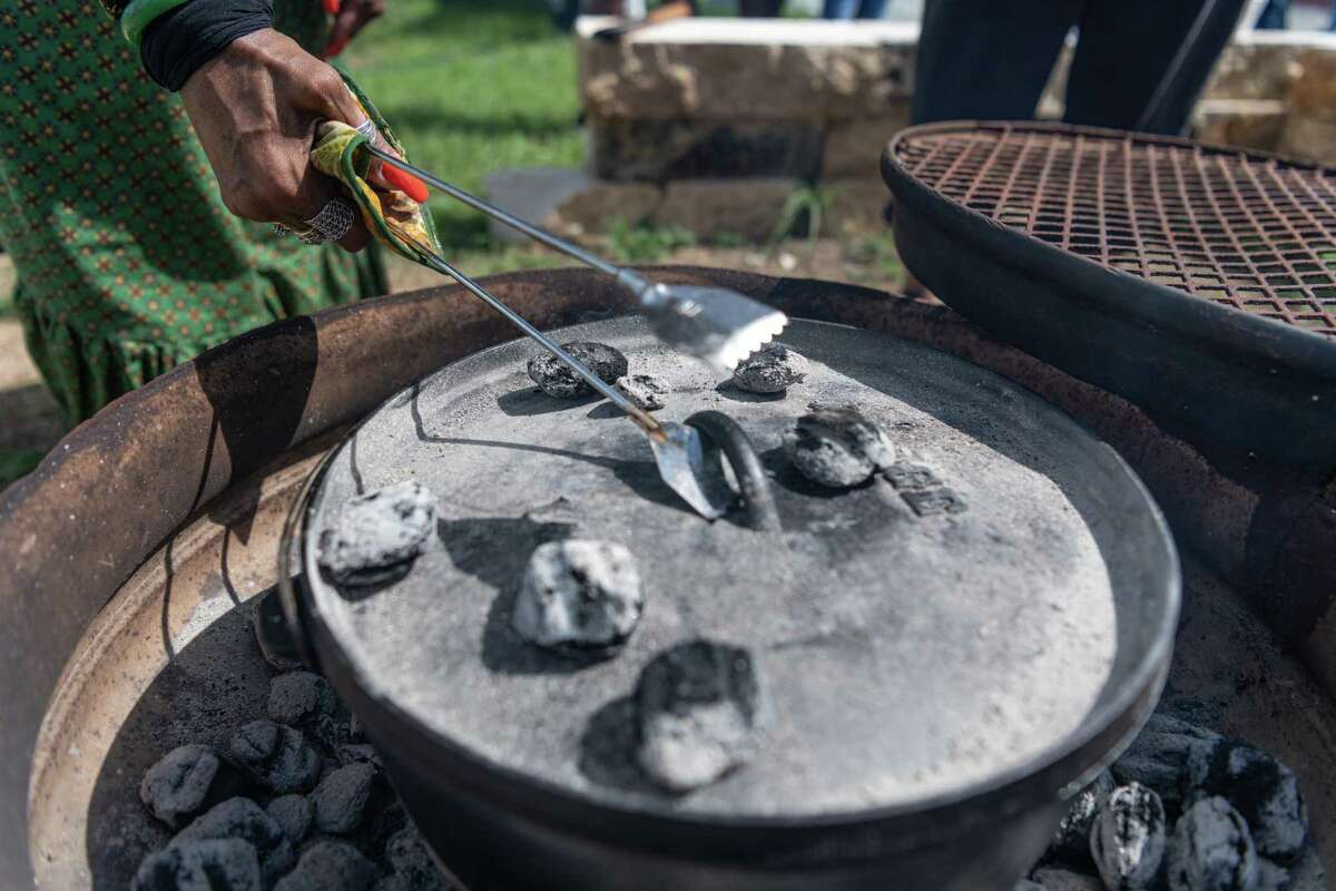 Mary Hardemon, 66, cooks Cowboy Cobbler in a dutch oven to demonstrate how many frontiersmen would've prepared food while on-trail. The San Antonio African American Community Archive and Museum hosted a Legacy Day on Friday morning for children to learn about Buffalo Soldiers, Black U.S. Army troops who served on the frontier after the Civil War, and Black cowboys who herded cattle to help feed a growing nation.