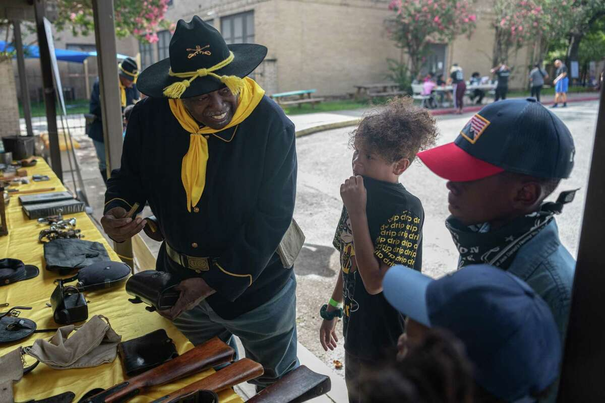 Wearing a Buffalo Soldier Cavalry uniform, Leslie Clay, 74, shows a group of young children a shell casing from a frontier-era weapon. The San Antonio African American Community Archive and Museum hosted a Legacy Day on Friday morning for children to learn about Buffalo Soldiers, Black U.S. Army troops who served on the frontier after the Civil War, and Black cowboys who herded cattle to help feed a growing nation