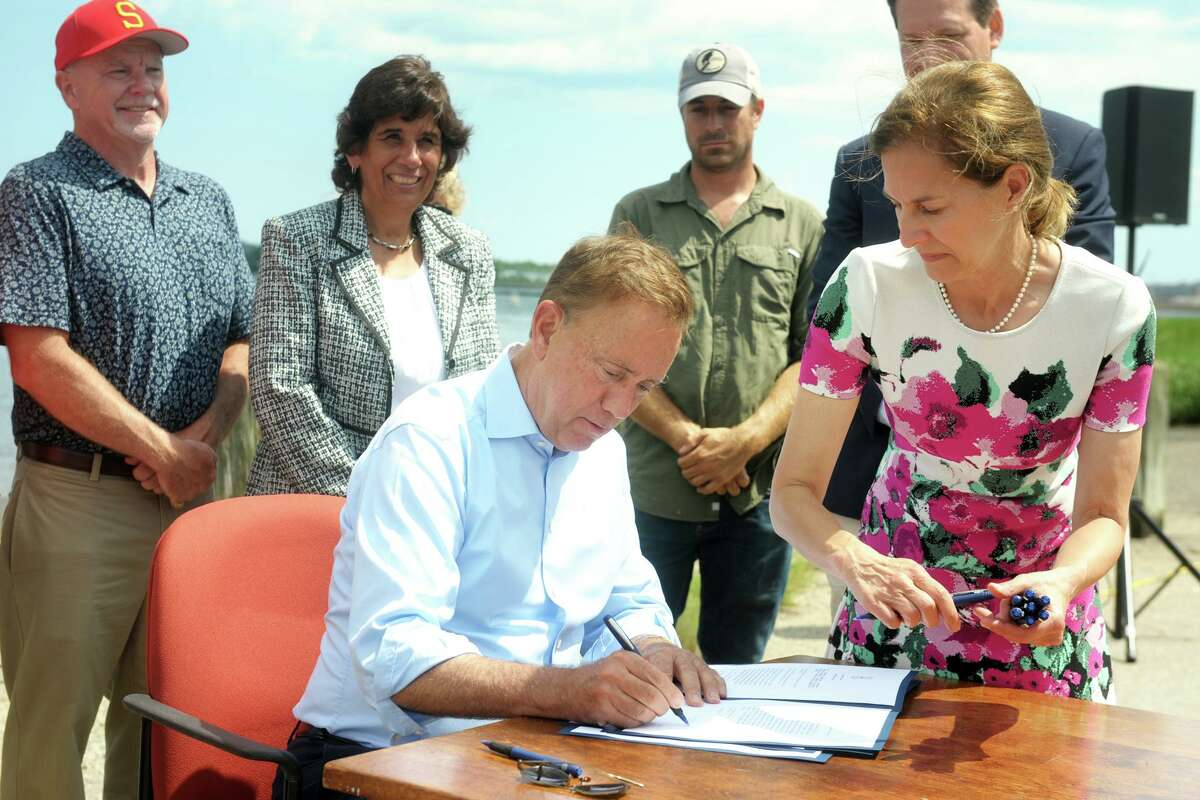 Governor Ned Lamont signs a legislative bill that will implement new policies designated to support continued growth of the state's shellfish industry at new conference in Stratford, Conn. July 23, 2021.