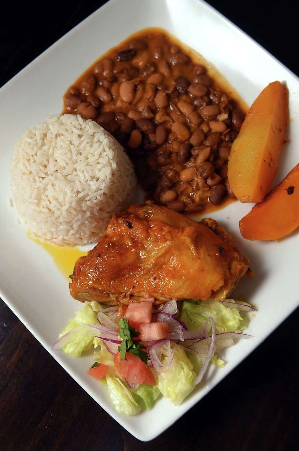 Roasted chicken with rice, beans, potatoes and salad.