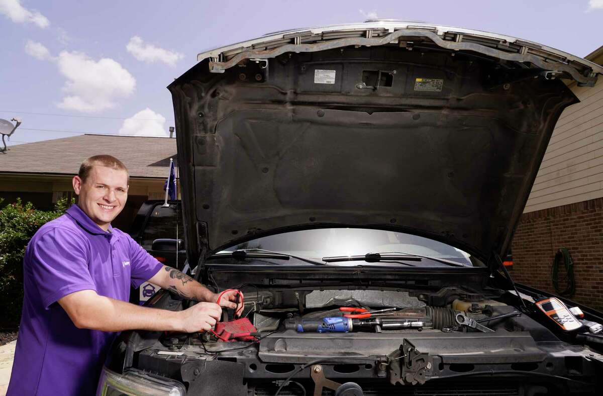 Ford Davis, a FixMyCar mechanic, demonstrates taking a battery voltage reading on his work vehicle Friday, July 23, 2021 in Tomball. FixMyCar sends mobile mechanics to your location for auto repairs.