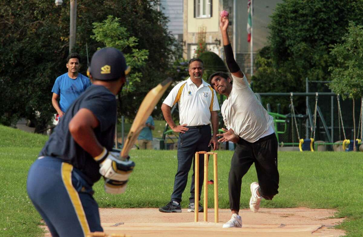 Bowler Sai Vemireddy, a member of the Mad Dogs Cricket Club, throws the ball to a batter during team practice at Mad Dog Park in Greenwich, Conn., on Thursday July 15, 2021. The club, which formed in 1990, has roughly 100 members, many of whom are expats from South Asia, South Africa, Australia, New Zealand and the UK.