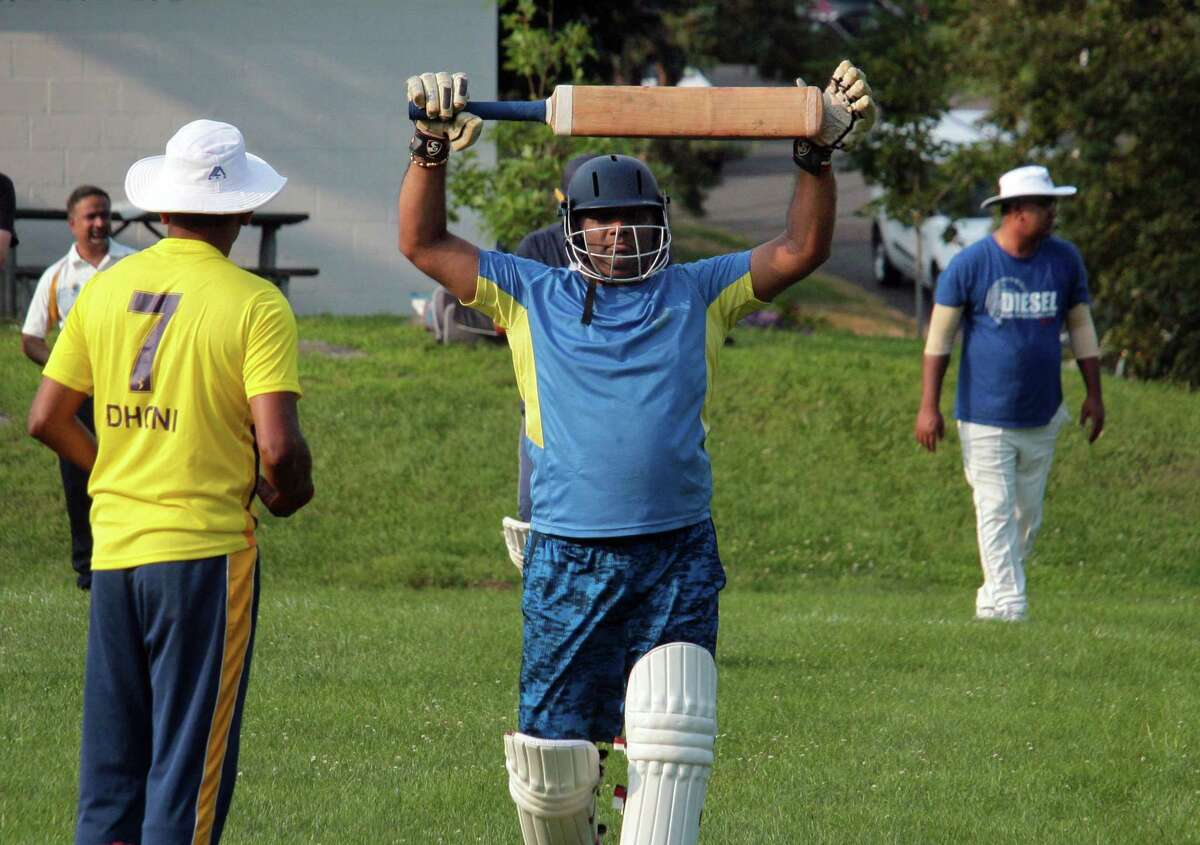 Batter Sai Niranjan, a member of the Mad Dogs Cricket Club, stretches as he walks up to play during team practice at Mad Dog Park in Greenwich, Conn., on Thursday July 15, 2021. The club, which formed in 1990, has roughly 100 members, many of whom are expats from South Asia, South Africa, Australia, New Zealand and the UK.