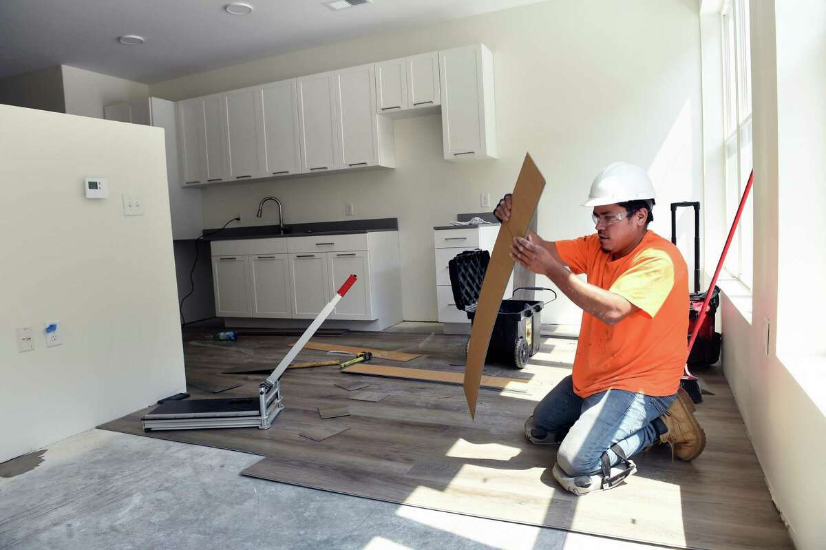 Jairo Mendoza installs luxury vinyl tile in a premium studio apartment at the Olive & Wooster Apartments in New Haven on July 22, 2021.