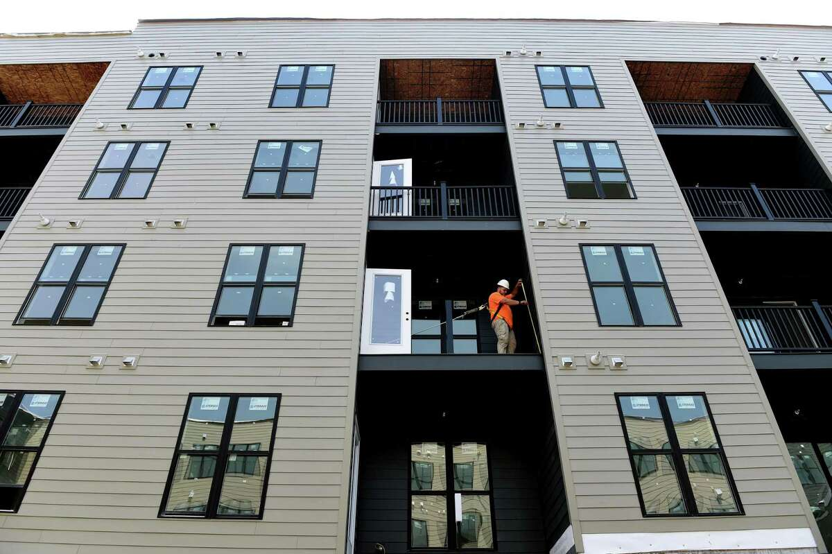 Measurements are taken for a railing on the patio of an apartment overlooking the Sports Courtyard of the Olive & Wooster Apartments in New Haven on July 22, 2021.