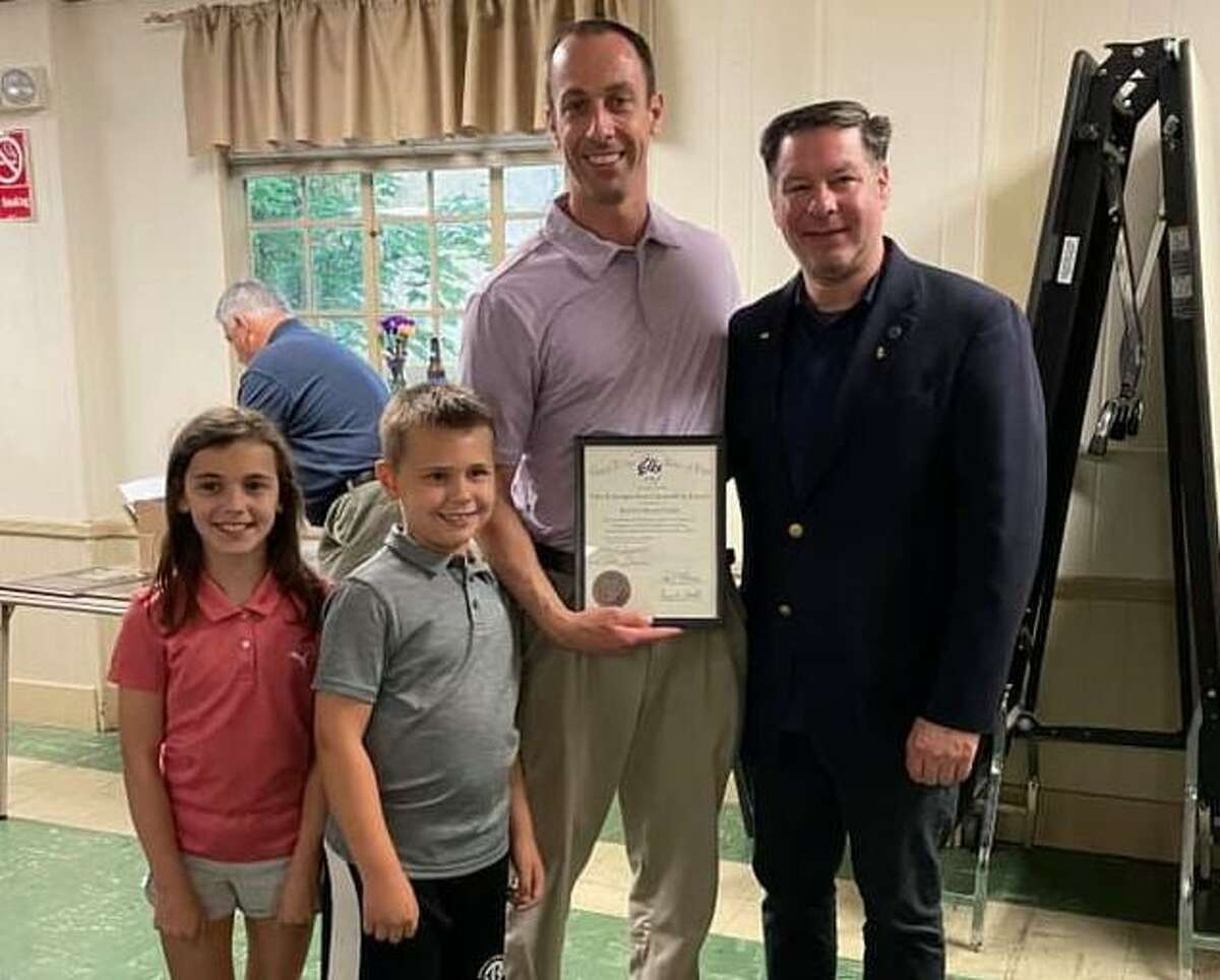 Robert Kozlowsky shows off his Distinguished Citizenship of the Year Award, which he received from the Bridgeport Elks Lodge 36 and the Grand Lodge, Benevolent Protective Order of Elks. Pictured with Kozlowsky are his children Regan and Kenneth, and Elks' Exalted Ruler William Russell