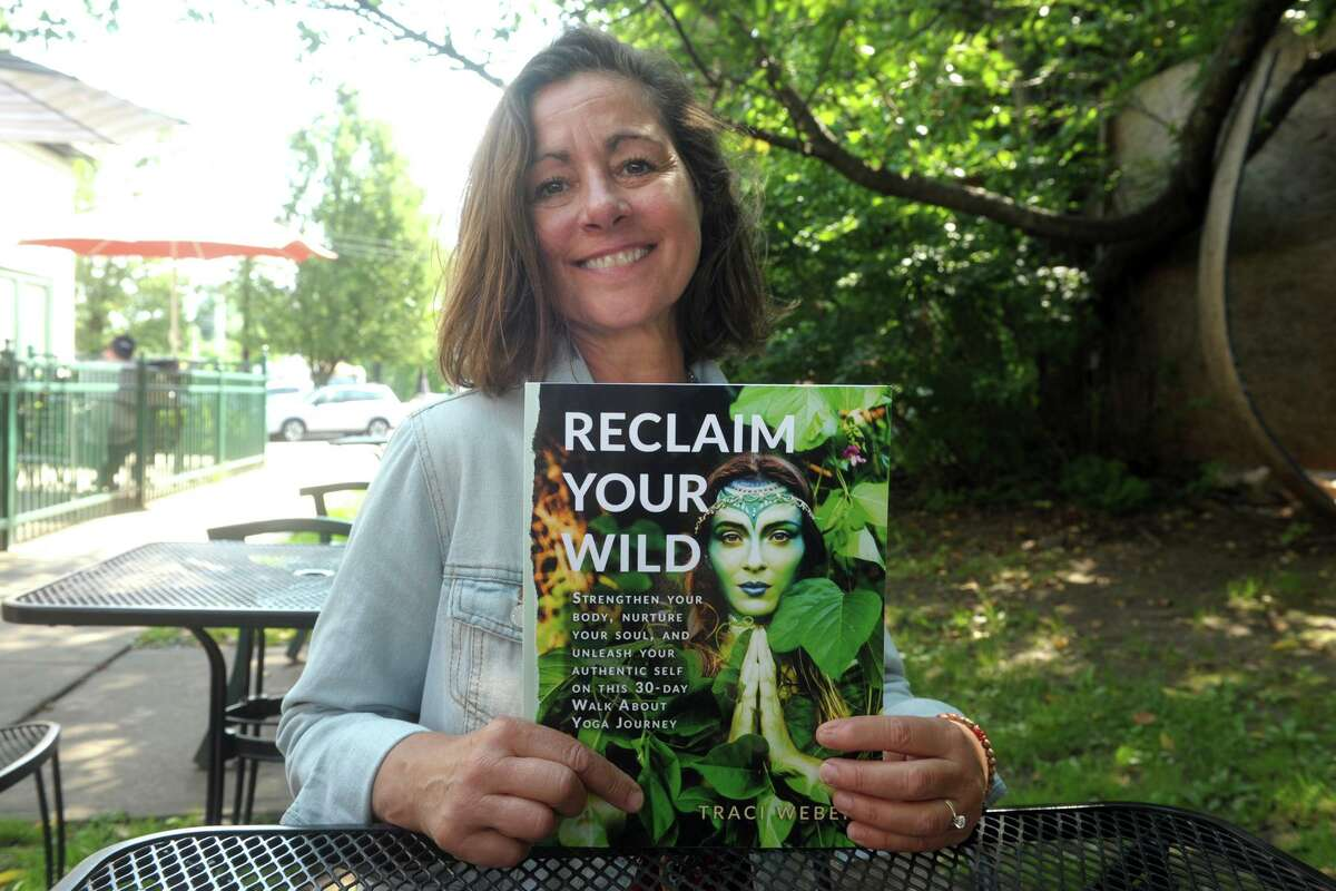 """Traci Weber poses with a copy of her book """"Reclaiming Your Wild"""" in Milford, Conn. July 22, 2021."""