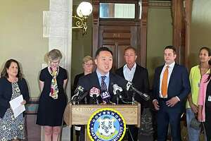 Connecticut Attorney General William Tong, center, speaks during a press conference at the state Capitol in Hartford on Wednesday, July 21, 2021 to announce Connecticut's participation in a $26 billion national settlement with AmerisourceBergen, Cardinal Health, McKesson and Johnson & Johnson related to their alleged roles in the opioid crisis.