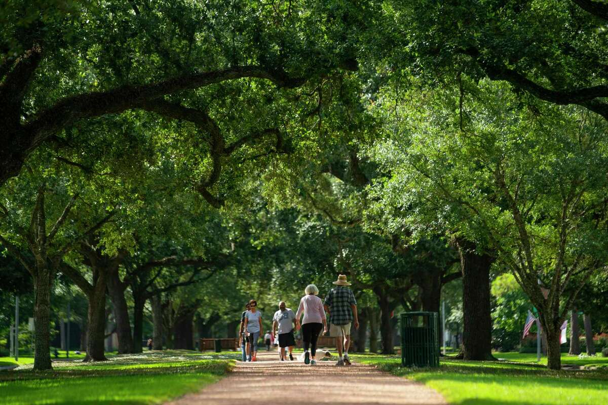 """People walk down the path at the center of Tanglewood Road on Thursday, July 22, 2021, in Houston. A new report by the organization American Forests addressed """"tree equity"""" in the nation's cities. The study finds tree inequity in basically every city, including Houston, grounded in historical redlining policies."""