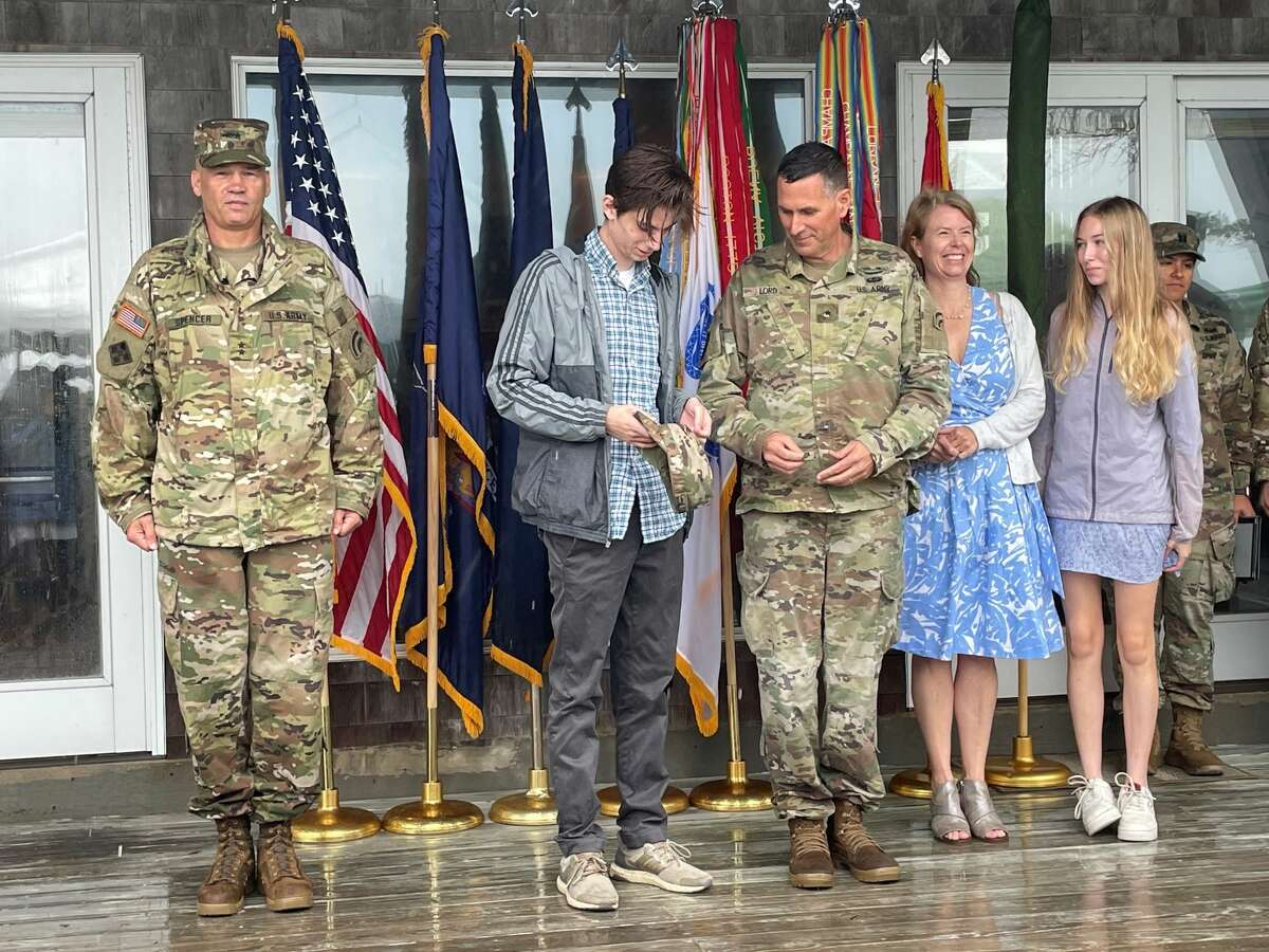 New York Army National GuardSam Lord, son of newly promoted Brig. Gen. Nathan Lord rank insignia on his dad's hat, during a ceremony as the Nathan's wife, Sarah and daughter Eizabeth as well as Maj. Gen. Thomas Spencer, left watch.