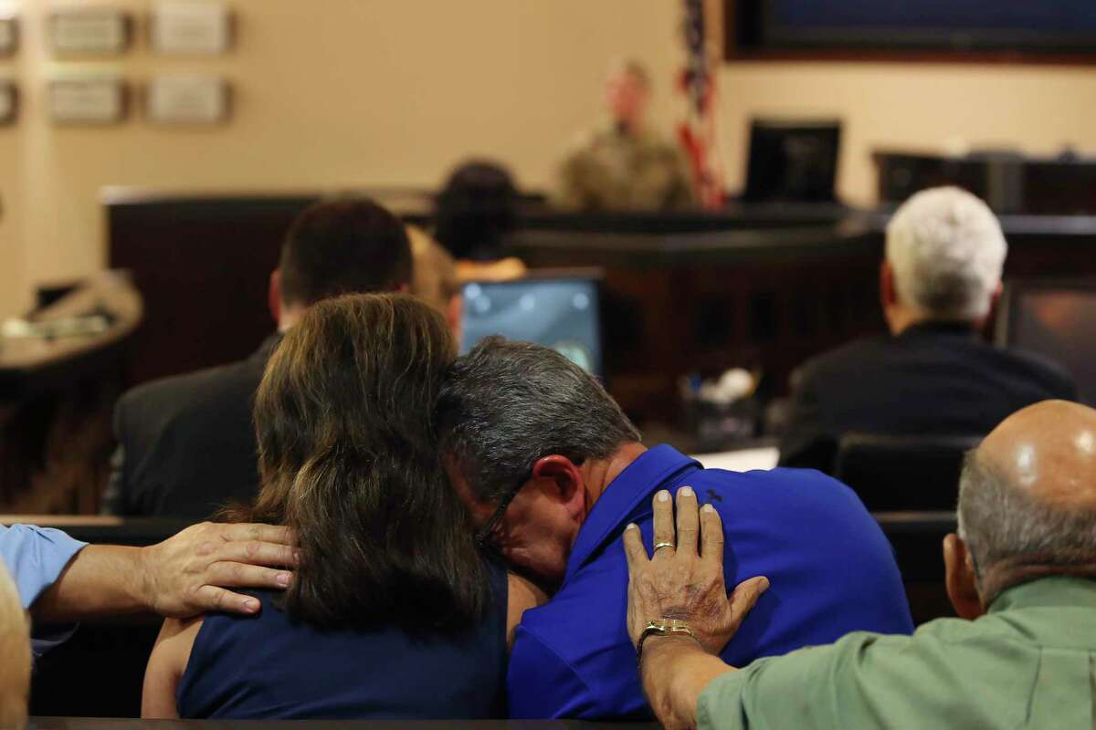 Family and friends of San Antonio police Detective Benjamin Marconi comfort each other during testimony on Friday.