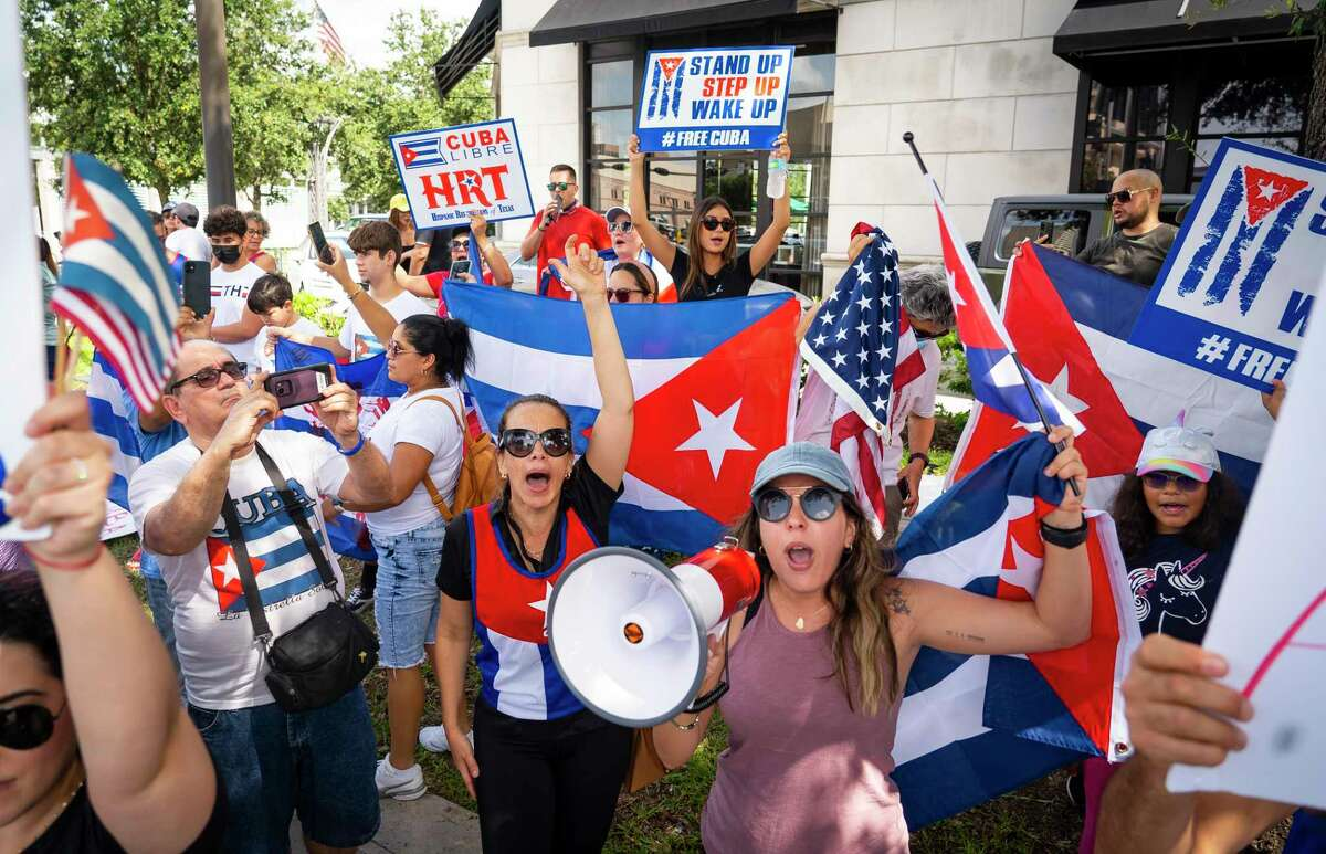 Magela Martinez, left, and Yolanda Luis, right, lead a chant during a rally to raise awareness about current upheaval against the government in Cuba and the subsequent crackdown, during a demonstration at the corner of Westheimer Road and Post Oak Boulevard on Saturday, July 17, 2021, in Houston.