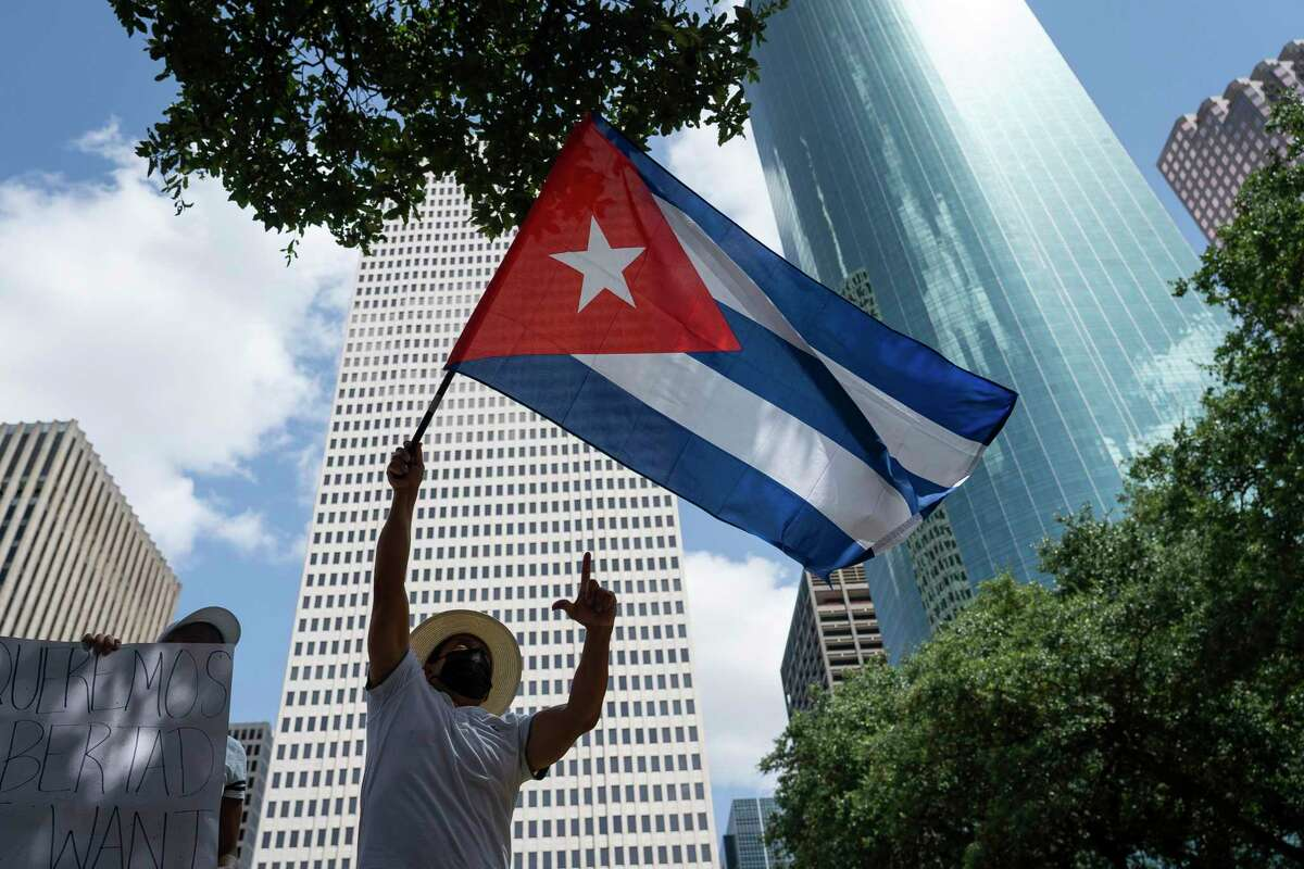 People rally on the steps of Houston city hall on Saturday, July 17, 2021, to try and raise awareness about unrest in Cuba.