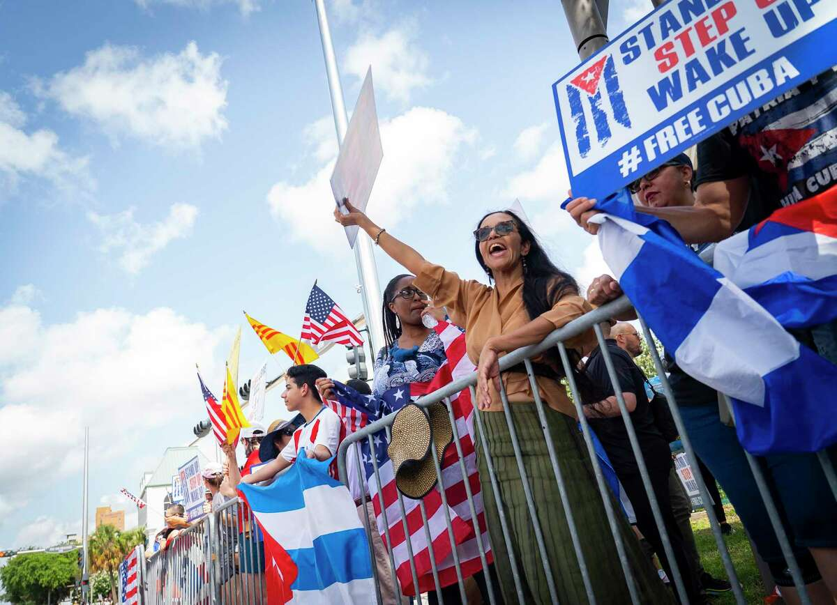 People rally to raise awareness about current upheaval against the government in Cuba and a subsequent crackdown, during a demonstration at the corner of Westheimer Road and Post Oak Boulevard on Saturday, July 17, 2021, in Houston.