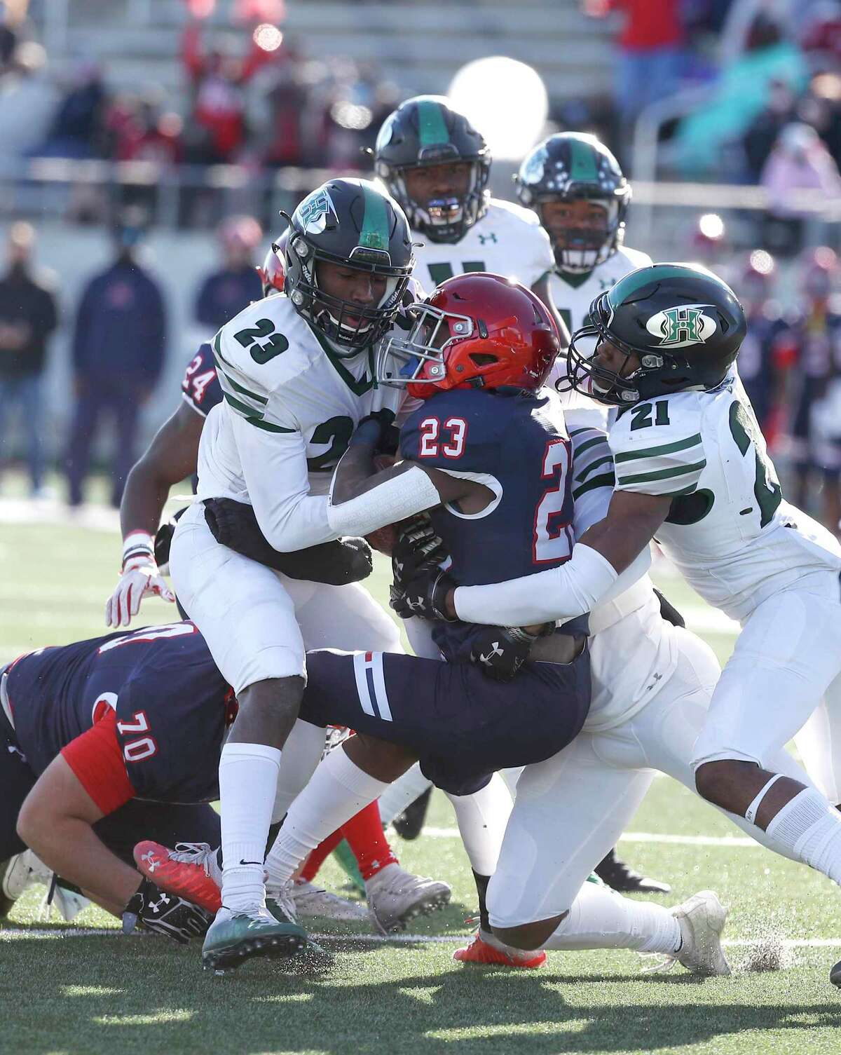 Manvel Mavericks Ty Harris (23) is tackled by Fort Bend Hightower Hurricanes Julian Payne (23) and Matthew Aneke (21) during the first half of a 5A D1 high school football game at Freedom Field, Thursday, December 24, 2020, in Arcola.