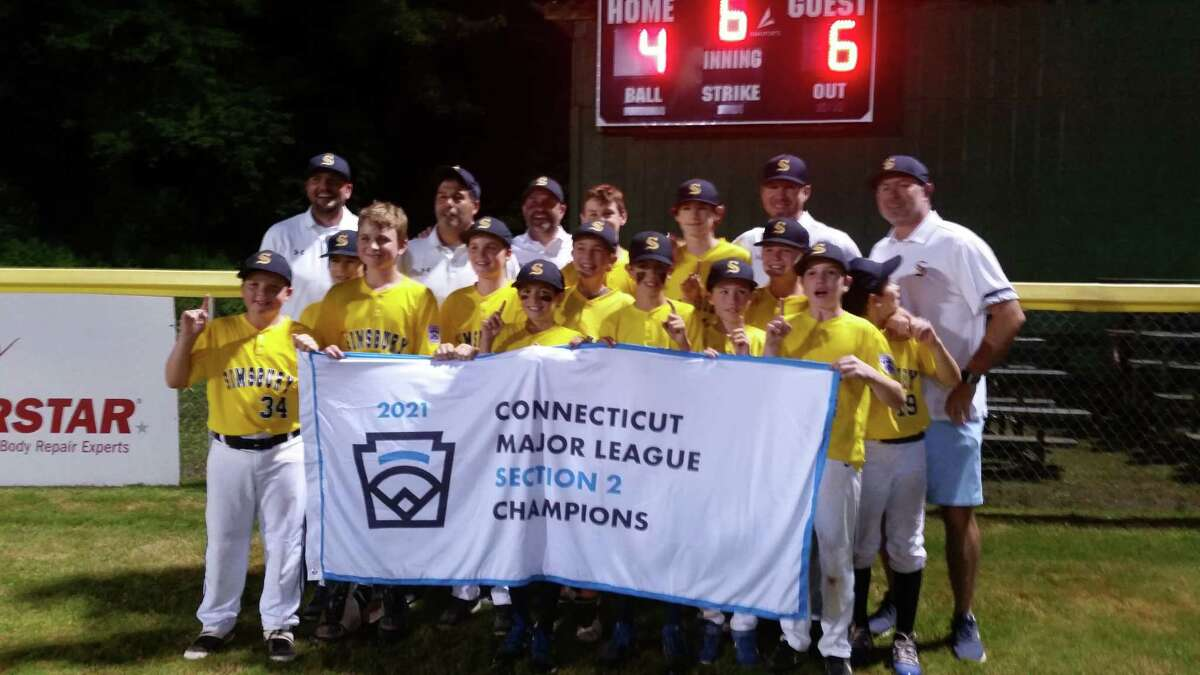 Simsbury players celebrate with the championship banner after winning the Connecticut Little League Section 2 title on Friday night.