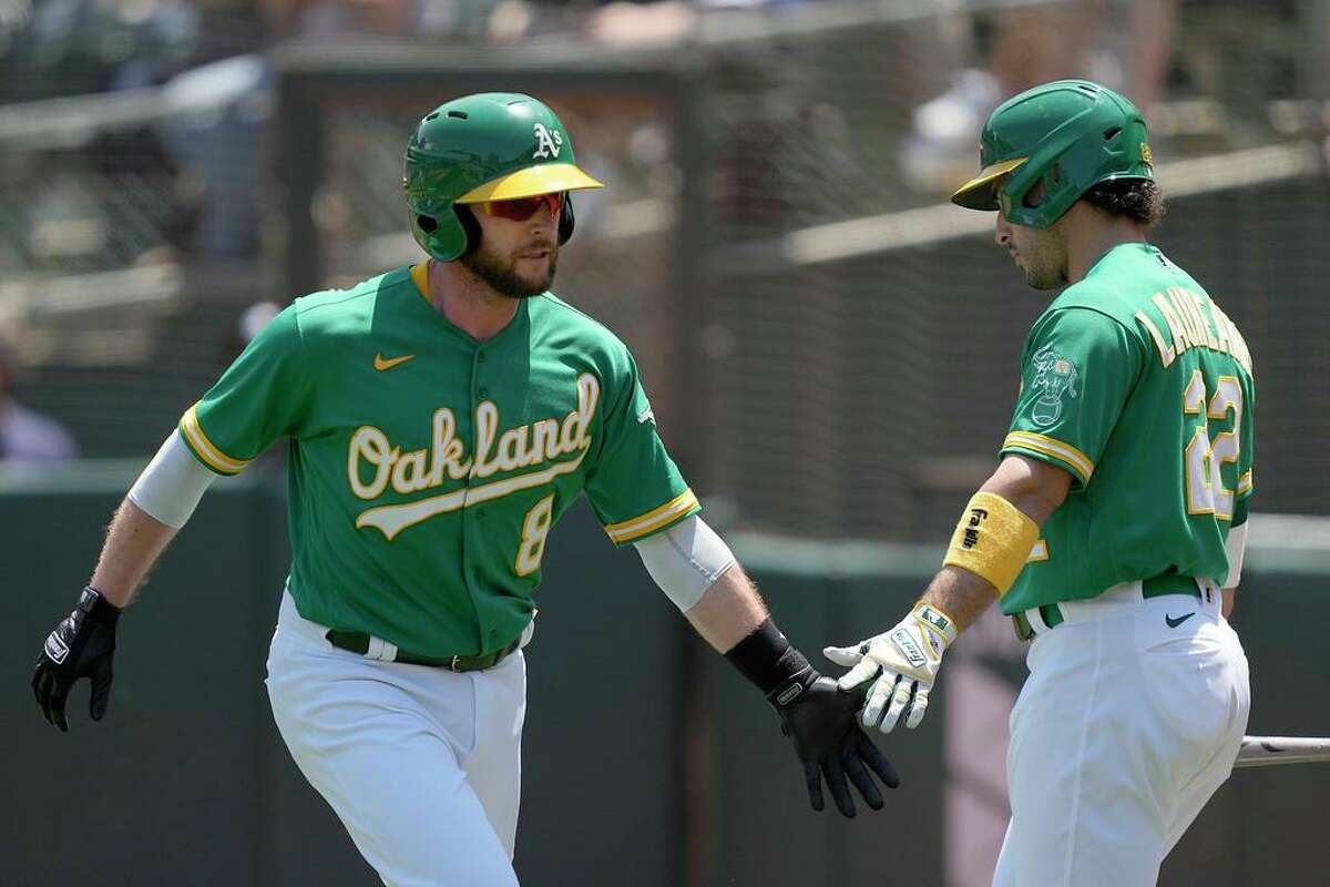 Oakland Athletics' Jed Lowrie (8) is congratulated by Ramon Laureano (22) after scoring a run against the Cleveland Indians during the second inning of a baseball game Sunday, July 18, 2021, in Oakland, Calif. (AP Photo/Tony Avelar)