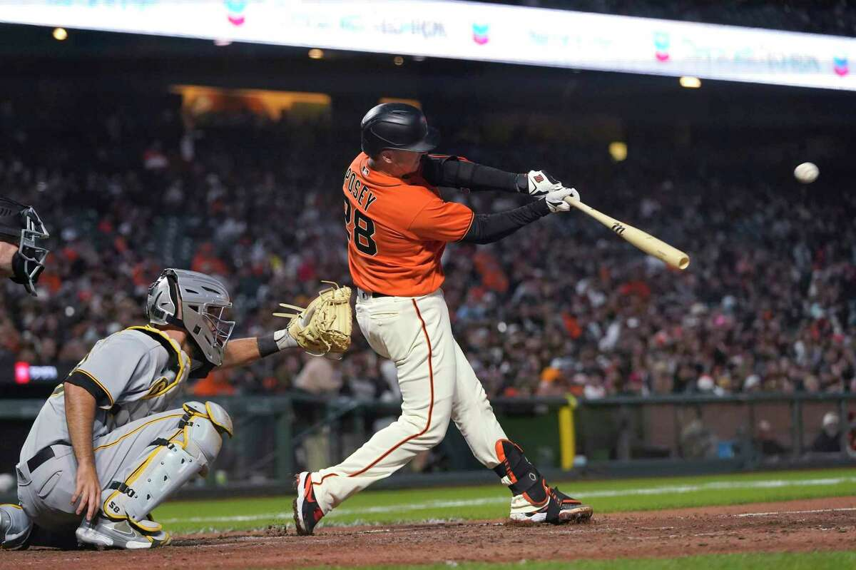 San Francisco Giants' Buster Posey hits a double in front of Pittsburgh Pirates catcher Jacob Stallings during the sixth inning of a baseball game in San Francisco, Friday, July 23, 2021. (AP Photo/Jeff Chiu)