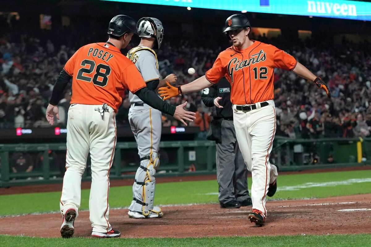 San Francisco Giants' Alex Dickerson (12) celebrates after hitting a two-run home run that scored Buster Posey (28) against the Pittsburgh Pirates during the sixth inning of a baseball game in San Francisco, Friday, July 23, 2021. (AP Photo/Jeff Chiu)