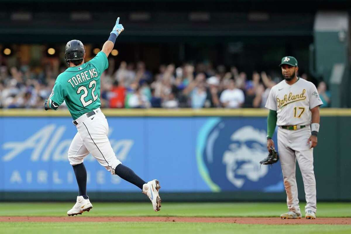 Seattle Mariners' Luis Torrens (22) points as he runs the bases past Oakland Athletics shortstop Elvis Andrus (17) after hitting a solo home run during the second inning of a baseball game Friday, July 23, 2021, in Seattle. (AP Photo/Ted S. Warren)