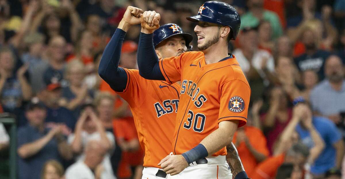 Houston Astros left fielder Kyle Tucker (30) is greeted by Houston Astros shortstop Carlos Correa (1) at home plate after clearing the bases with a three-run home run to right field during the third inning of a game between the Houston Astros and Texas Rangers on Friday, July 23, 2021, at Minute Maid Park in Houston.