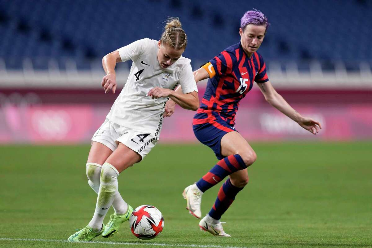 New Zealand's CJ Bott (4) battles for the ball against United States' Megan Rapinoe (15) during a women's soccer match at the 2020 Summer Olympics, Saturday, July 24, 2021, in Saitama, Japan. (AP Photo/Martin Mejia)