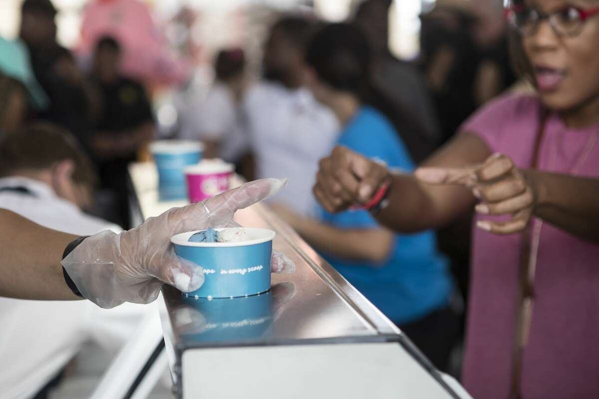 Ice cream is served up during the grand opening of Howdy Homemade Ice Cream Thursday, July 22, 2021 in Katy. Hundreds of people flocked to the new ice cream franchise, owned and run by Houston rap artist, activist and philanthropist Trae tha Truth and his business partner Roderick Batson. The shop's mission is not just to serve up hand scooped ice cream but to also give employment opportunities to adults with special needs.