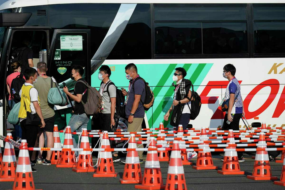A maze of cones lead people onto a bus at the main transport hub at the 2020 Summer Olympics in Tokyo. Getting to and from events is often a confusing endeavor.