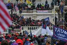 Participants in a pro-Trump mob take over the inaugural stage at the Capitol on Jan. 6.