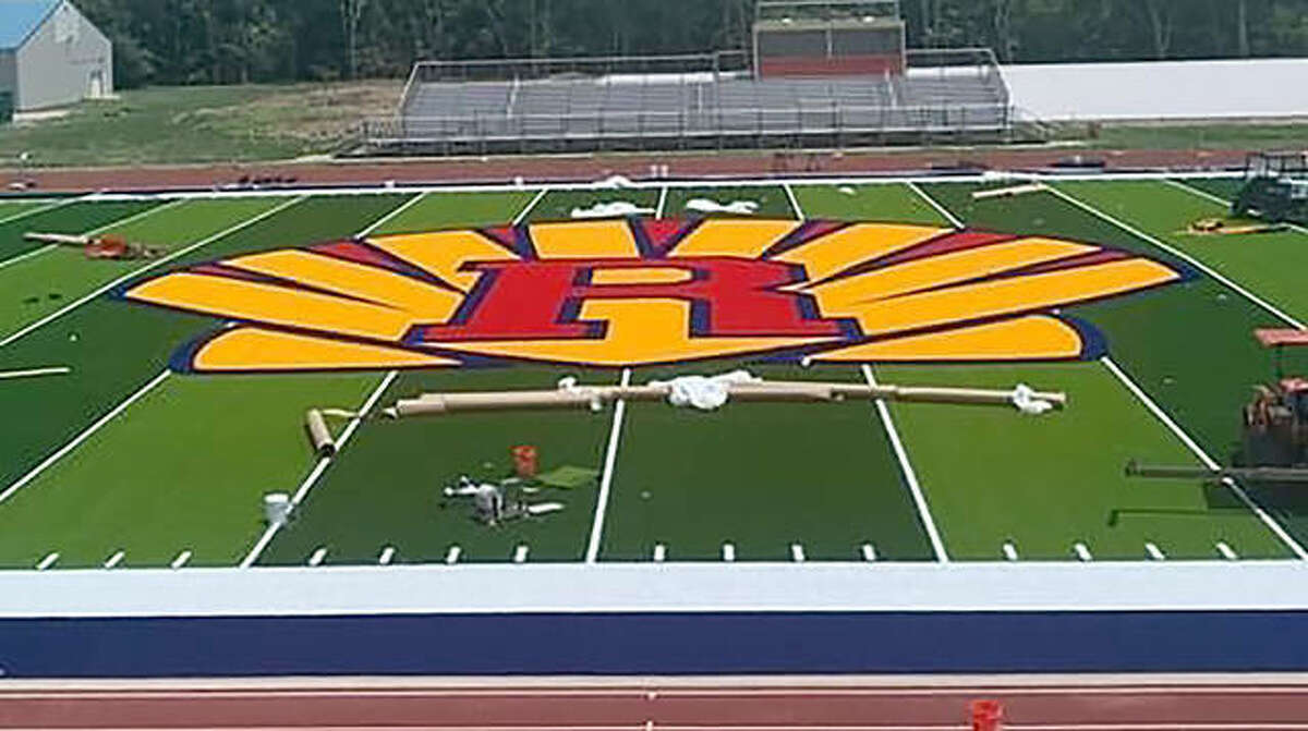 Work on the new Astroturf football field at Roxana High School continues with the installation of the RHS Shells logo in the center of the field Saturday.