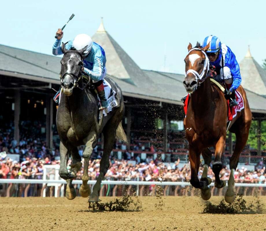 Maracuja with jockey Ricardo Santana Jr., left raises his whip in victory after beating Malathaat with jockey John Velazquez to the wire to win the 105th running of The Coaching Club American Oaks at The Saratoga Race Course Saturday July 24, 2021 in Saratoga Springs, N.Y.  Photo by Skip Dickstein/Tim Lanahan Photo: Skip Dicsktein/Tim Lanahan