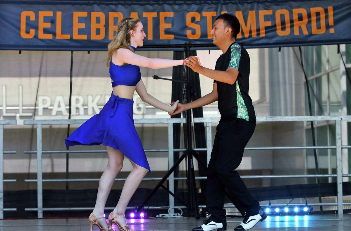 """Amanda Duvall and Jason Ramos, with the dance company Baila Con Gusto in New Haven, perform salsa dancing during Stamford Town Center's first """"Block Party: A Celebration of Culture and Community"""" event at Restaurant Plaza at Stamford Town Center in Stamford, Conn., on Saturday July 24, 2021. The party will continue Sunday with food, activities and performances designed to celebrate local diversity as area residents inch toward post-pandemic normalcy."""