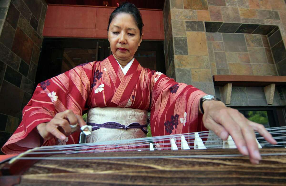 """Masami Morimoto, of NYC, warms up playing the koto before performing during Stamford Town Center's first """"Block Party: A Celebration of Culture and Community"""" event at Restaurant Plaza at Stamford Town Center in Stamford, Conn., on Saturday July 24, 2021. The party will continue Sunday with food, activities and performances designed to celebrate local diversity as area residents inch toward post-pandemic normalcy."""