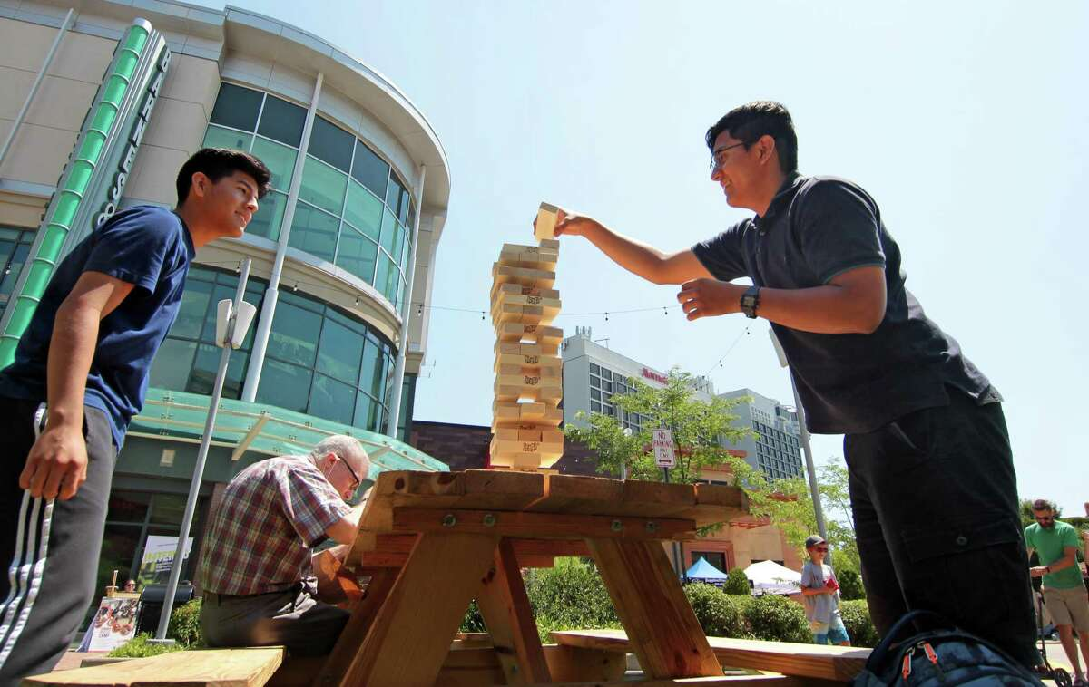 """Clockwise from above, Joaquin Diaz-Huerta, left, and Elvis Coy take turns playing a game of Jenga; Dancer Emily Soraluz, 13, gets help from her mom Elsa Martinez to get ready to perfom; during Stamford Town Center's first """"Block Party: A Celebration of Culture and Community"""" event at Restaurant Plaza at Stamford Town Center in Stamford, Conn., on Saturday July 24, 2021. The party will continue Sunday with food, activities and performances designed to celebrate local diversity as area residents inch toward post-pandemic normalcy."""