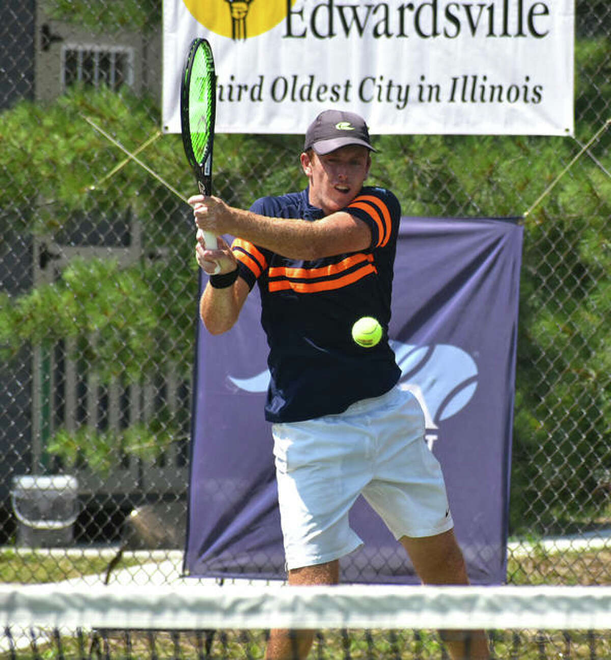 Reese Stalder connects for a backhand shot during the first set of the doubles championship match at the Edwardsville Futures on Saturday.