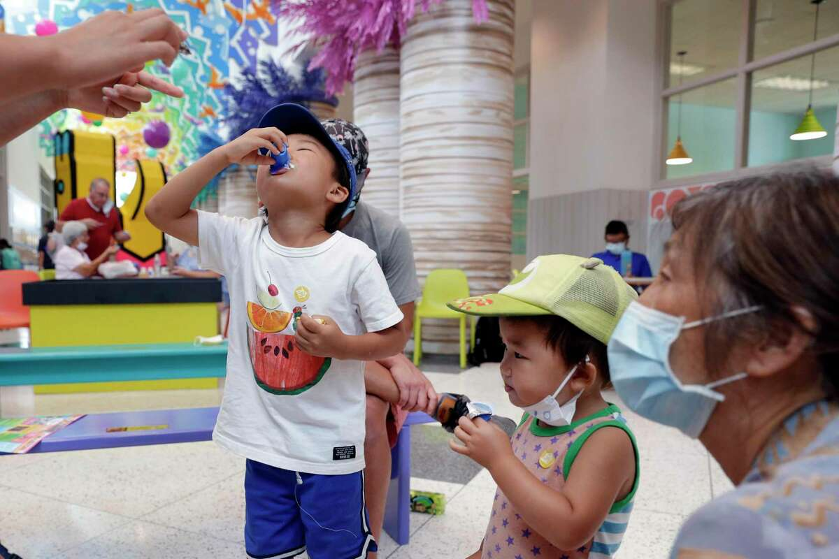 """Brothers Kaito Wang, age five, left, and Koen Wang, age two, right, slurp down their samples of home made ice cream made from coffee creamers during the """"I Scream for Ice Cream"""" food science demonstration, as part of the celebration of National Ice Cream Day at the Children's Museum of Houston Saturday, Jul. 24, 2021 in Houston, TX."""