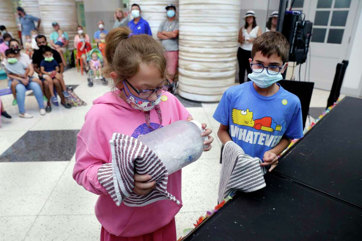 """Rosie Baker, age eight, left, and Anthony Bruno, age 10, right, take turns shaking a container full of ice, salt and coffee creamers as they make ice cream during the """"I Scream for Ice Cream"""" food science demonstration, as part of the celebration of National Ice Cream Day at the Children's Museum of Houston Saturday, Jul. 24, 2021 in Houston, TX."""