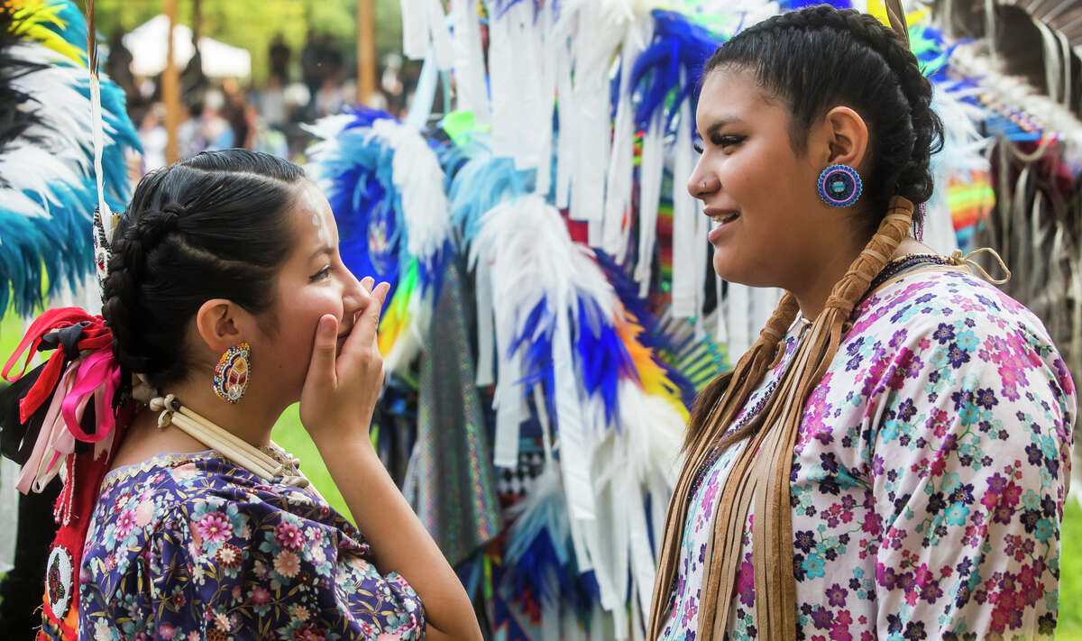 Miah Perez, 13, left, and Rainah Perez, 14, right, chat after performing in the grand entrance during the 37th Annual Saginaw Chippewa Pow Wow Friday, July 23, 2021 at the Saginaw Chippewa Tribal Campground in Mount Pleasant. (Katy Kildee/kkildee@mdn.net)
