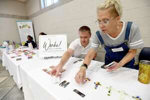 Russell Whatley and Honey Staudenmier with Ability Central Works arrange some of their clients' creations during the ADA Celebration Day event Friday at Central Park.  Photo made Friday, July 23, 2021 Kim Brent/The Enterprise